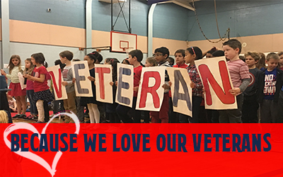 Children holding Veteran sign